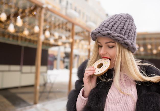 Urocza blondynka gryzie smaczne piernikowe ciasteczko na tle lekkiej dekoracji na placu w kijowie