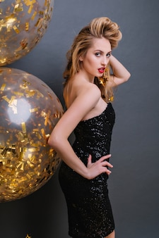 Urocza blondynka oglądająca się przez ramię i bawiąca się włosami podczas imprezowej sesji zdjęciowej. szczupła jasnowłosa dama ma na sobie czarną sukienkę ze złotymi balonami.