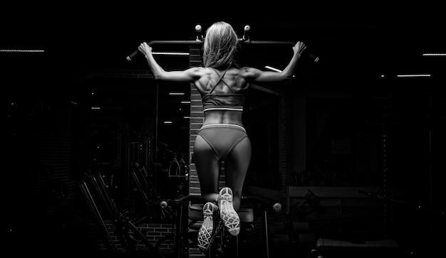 Urocza blondynka podciąga się na bar. pojęcie sportu, siłowni, odzieży sportowej, fitness. przygotowanie do zawodów. widok z tyłu. różne środki przekazu