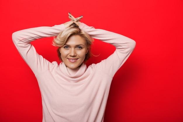 Urocza blondynka pozowanie z rękami do góry i pięknie się uśmiecha na czerwonym tle