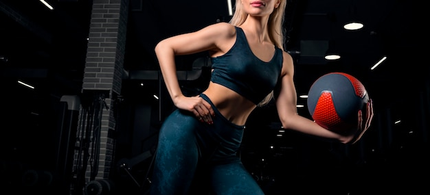 Urocza blondynka pozuje na siłowni z piłką fitness. przedni widok. pojęcie sportu, kulturystyki, fitnessu. różne środki przekazu