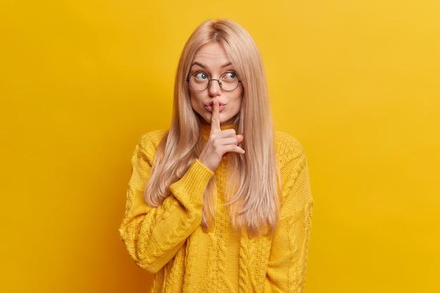 Urocza blondynka robi gest ciszy, ukrywa tajemnicę, mówi poufne informacje, ma tajemniczą minę ubrana w zwykły strój, prosi, aby nie hałasować. uciszenie i tajemnica