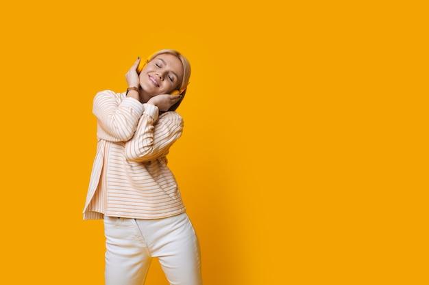 Urocza blondynka słuchająca rozmyślań przez słuchawki na żółtej ścianie studia z wolną przestrzenią
