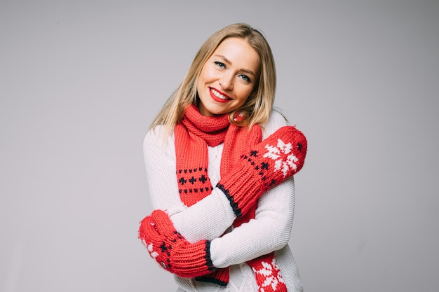Urocza blondynka w czerwonym szaliku z dzianiny i rękawiczkach obejmujących się i uśmiechnięta