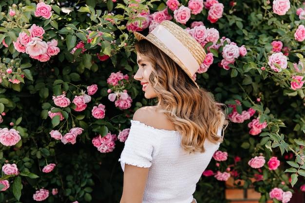Urocza blondynka w kapeluszu lato patrząc na kwiaty z uśmiechem. urocza kręcona kobieta relaksująca się podczas sesji zdjęciowej z różami.