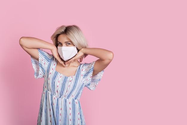 Urocza blondynka w masce medycznej w sukience pozuje na różowej ścianie studia z wolną przestrzenią