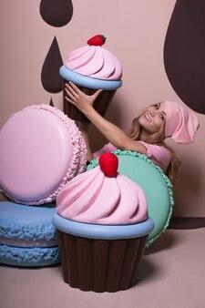 Urocza blondynka w różowej czapce i koszulce bawi się dużymi makaronikami i babeczkami w studio