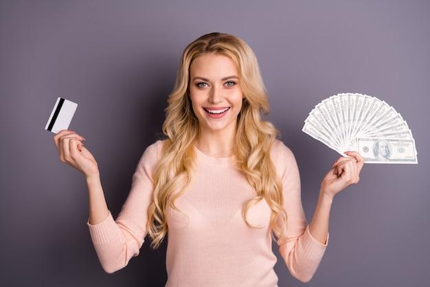 Urocza blondynka w różowym swetrze pozuje z pieniędzmi na fioletowej ścianie