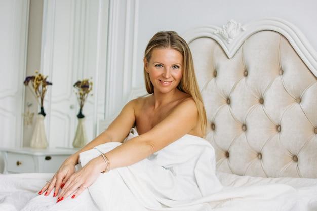 Urocza blondynka z długimi jasnymi włosami w bieliźnie, siedząc na łóżku w jasnym, bogatym wnętrzu. koncepcja życia po czterdziestce