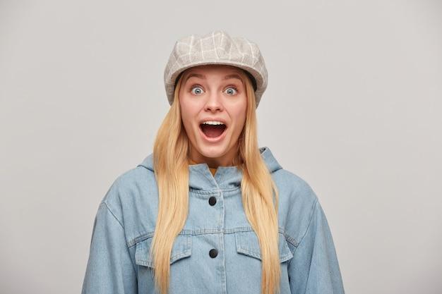 Urocza blondynka z długimi włosami, wygląda na zachwyconą, uradowaną i zdumioną, usta otwarte