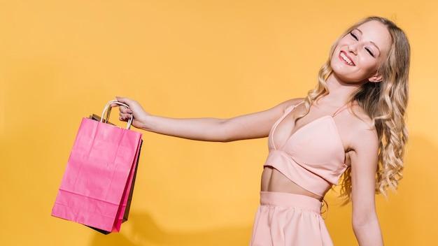 Urocza blondynka z kolorowymi torbami na zakupy