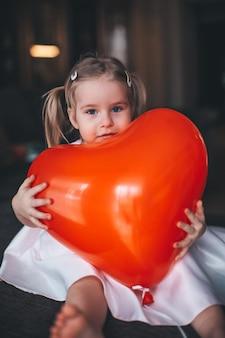 Urocza blondynki dziewczyna siedzi na ciemnym drewnianym konia stole i ściska czerwonego balon w kształcie serca w domu. koncepcja walentynki.