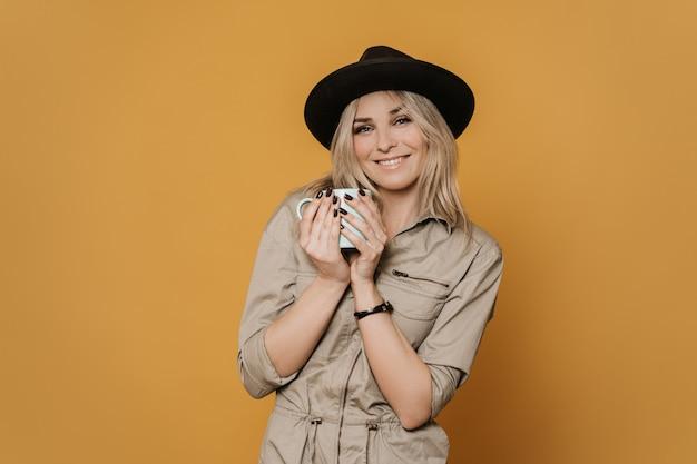 Urocza blondynki kobieta w przypadkowym kombinezonie i kapeluszowym ślicznym ono uśmiecha się, delikatnie trzymając filiżankę kawy, wygląda radośnie, na żółtym tle. koncepcja pozytywnych ludzi.