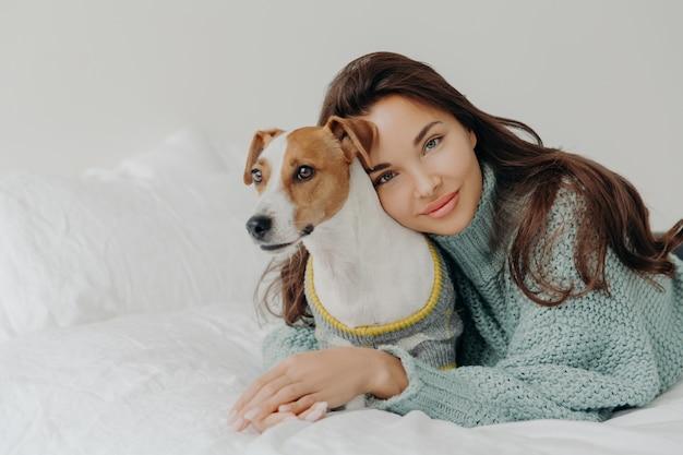 Urocza brunetka dama pochyla się w rodowodzie jack russel terrier, z miłością obejmuje zwierzaka, spędza razem czas