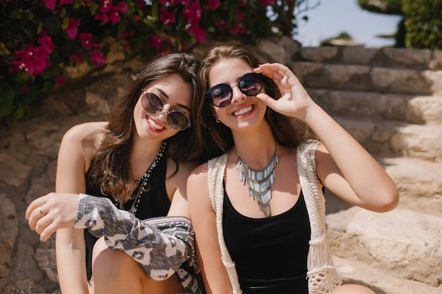 Urocza brunetka dziewczyna w okularach przeciwsłonecznych i modnym naszyjniku pozuje z piękną siostrą na przyrodę. urocze młode damy w stylowych czarnych strojach siedzące na zewnątrz po spacerze w parku