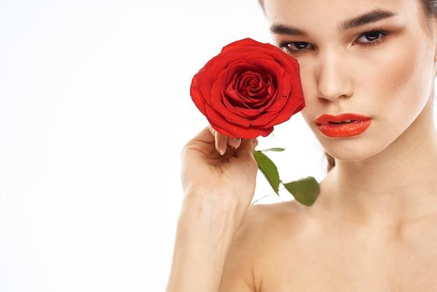 Urocza brunetka dziewczyna z makijażem na twarzy i czerwoną różą w dłoni.
