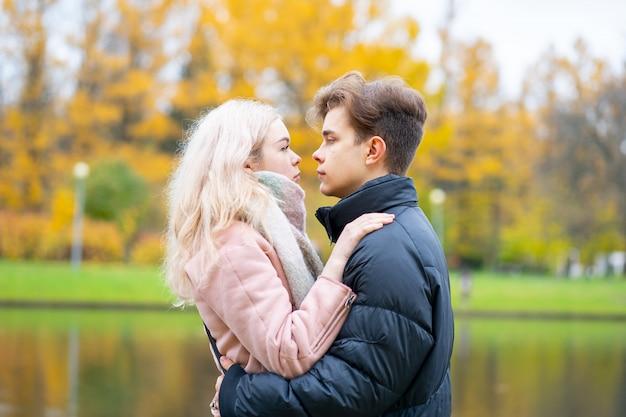 Urocza brunetka facet i ładna blond dziewczyna piją kawę i rozmawiają na randce. kochające nastolatki