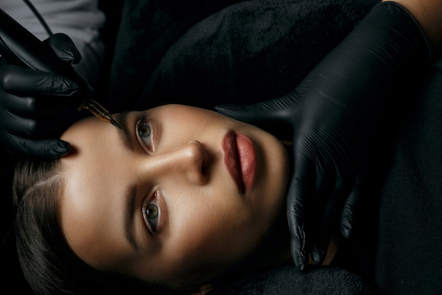 Urocza brunetka kobieta o permanentnej procedurze brwi w gabinecie kosmetycznym. widok z góry