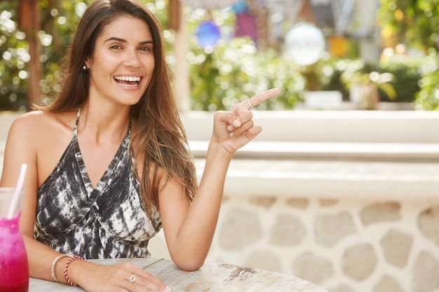 Urocza brunetka kobieta o szczęśliwym wyglądzie ubrana w letnie ubrania, siedzi w kawiarni, wskazuje palcem wskazującym na odległość, pije świeży koktajl