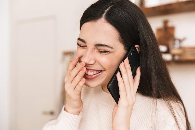 Urocza brunetka kobieta śmiejąc się, trzymając i rozmawiając na smartfonie w stylowej kuchni w domu