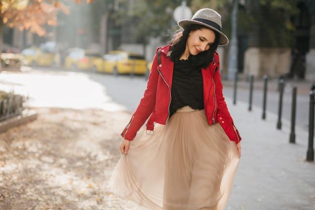 Urocza brunetka kobieta w długiej beżowej spódnicy spaceru po parku i patrząc w dół