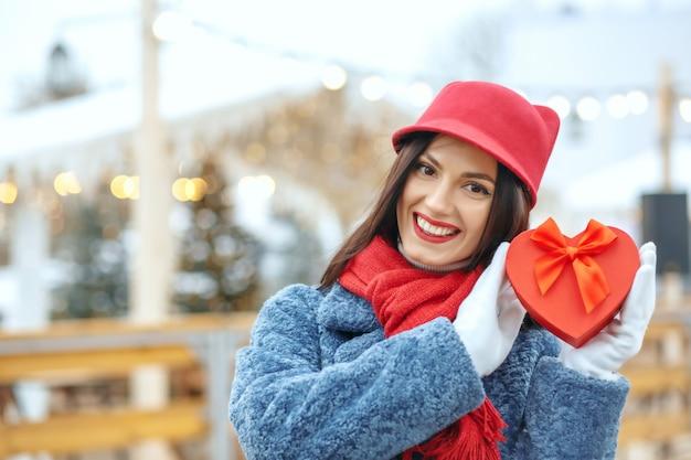 Urocza brunetka kobieta w płaszczu zimowym trzymająca pudełko na targach bożonarodzeniowych. miejsce na tekst