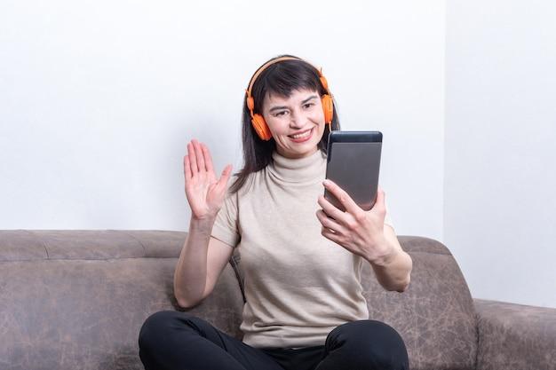 Urocza brunetka kobieta w pomarańczowych słuchawkach, prowadząca rozmowę wideo i pokazująca gest powitania lub pożegnania
