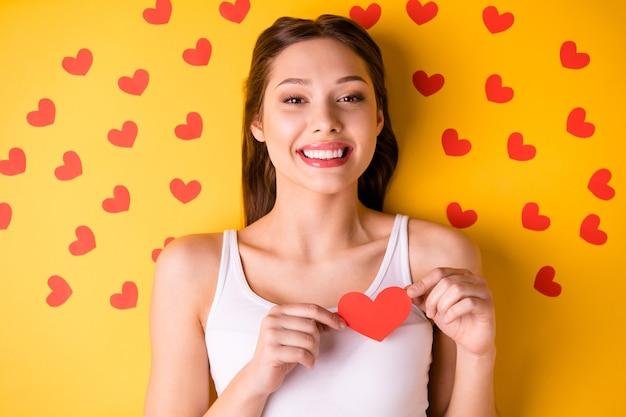 Urocza brunetka kobieta z czerwonymi ustami, pozowanie na żółtej ścianie