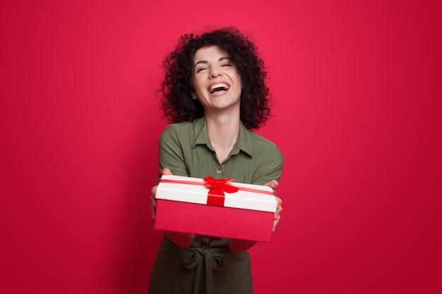 Urocza brunetka kobieta z kręconymi włosami, dając prezent na aparat uśmiecha się na czerwonej ścianie studio