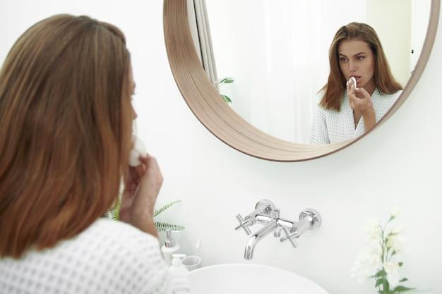 Urocza brunetka myje skórę wacikiem ze środkiem czyszczącym