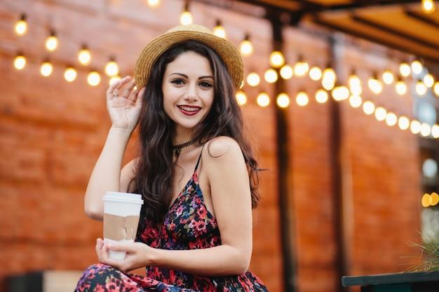 Urocza brunetka o ciemnych oczach i czerwonych ustach, ciesząca się wolnym czasem w stołówce, pijąc gorącą herbatę lub kawę