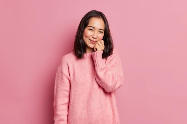 Urocza brunetka o wschodnim wyglądzie trzyma rękę na twarzy ma delikatny uśmiech wygląda na zadowoloną, że aparat ma dołeczki na różowych policzkach