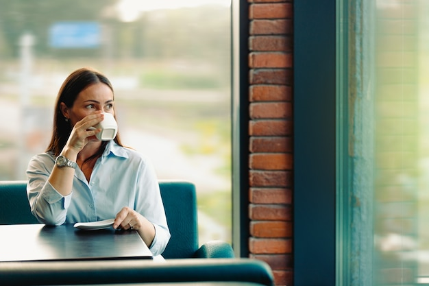 Urocza brunetka odpoczywa i pije kawę podczas przerwy w kawiarni. koncepcja odpoczynku w kawiarni w przerwie między pracą. zdjęcie z pustą przestrzenią.