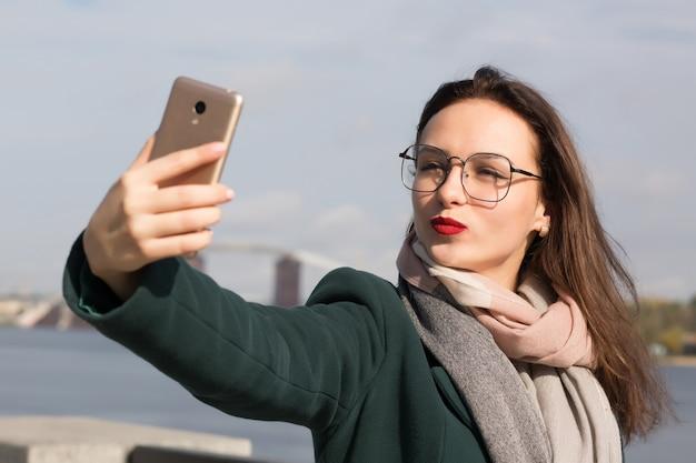 Urocza brunetka turystka robi sobie zdjęcie selfie na wybrzeżu rzeki w kijowie