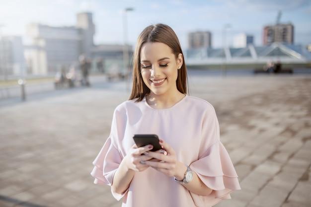 Urocza brunetka ubrała się elegancko, uśmiechając się i używając inteligentnego telefonu na dachu
