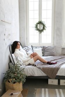 Urocza brunetka w ciepłej białej sukni odpoczywa na łóżku przy oknie ozdobionym wieńcem