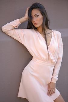 Urocza brunetka w lekkiej letniej sukience przy kamiennej ścianie