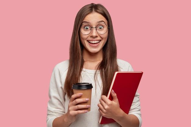 Urocza brunetka z podekscytowaną miną, patrzy ze szczęścia, nosi okrągłe okulary, trzyma czerwony podręcznik i wyjmuje kawę, reaguje na dobre wieści od kolegi z klasy, odizolowana na różowej ścianie
