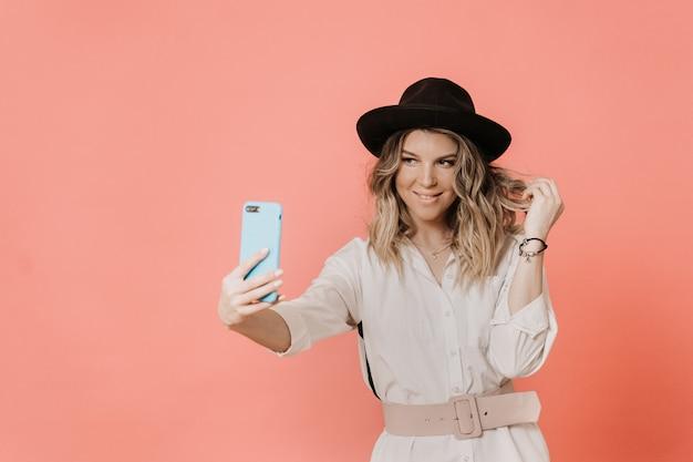 Urocza buźka blondynka w kapeluszu z rondem, białą bluzką i jasnoróżowym robi selfie, na różowym tle z miejsca kopiowania. styl i koncepcja zakupów.