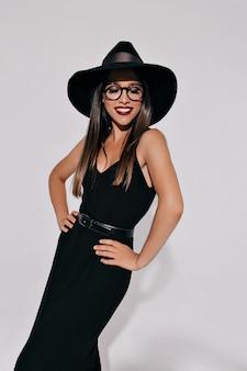 Urocza bystra kobieta w stroju czarownicy pozuje na izolowanej ścianie z pięknym uśmiechem. atrakcyjny stylowy model przygotowujący na imprezę halloweenową