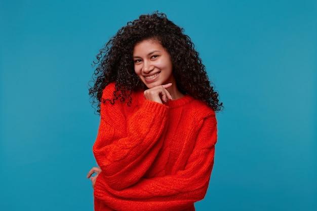 Urocza całkiem szczęśliwa uśmiechnięta dama w czerwonym swetrze z dzianiny pozuje na białym tle nad niebieską ścianą studia