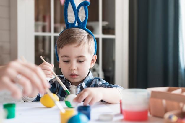 Urocza chłopiec maluje jajka na easter