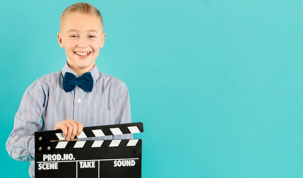 Urocza chłopiec mienia clapperboard kopii przestrzeń
