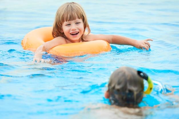 Urocza chłopiec pływa w basenie