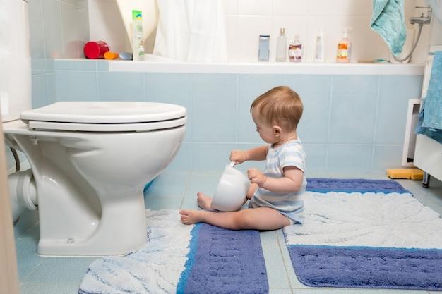 Urocza chłopiec siedzi na podłodze w łazience i bawi się papierem toaletowym