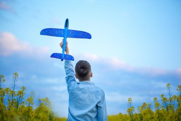 Urocza chłopiec trzyma zabawkarskiego samolot w jego ręce na zmierzchu w letnim dniu. widok z tyłu.