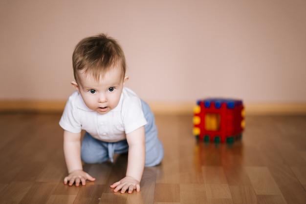 Urocza chłopiec uczy się czołgać się i bawić się w białej pogodnej sypialni. śliczny roześmiany dziecko czołgać się na sztuki macie. wnętrze pokoju dziecięcego, odzież i zabawki dla małych dzieci