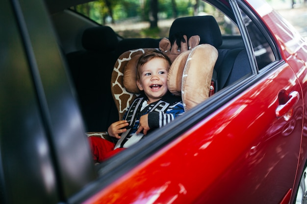 Urocza chłopiec w bezpiecznym foteliku samochodowym.