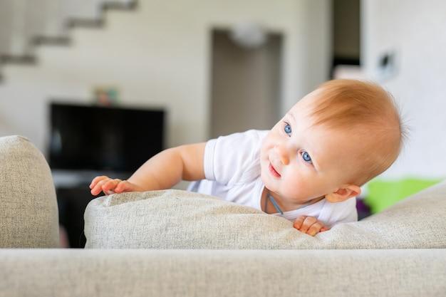Urocza chłopiec w białej pogodnej sypialni. nowonarodzone dziecko relaksuje na błękitnym łóżku. przedszkole dla małych dzieci.