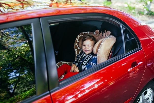 Urocza chłopiec w foteliku samochodowym bezpieczeństwa.
